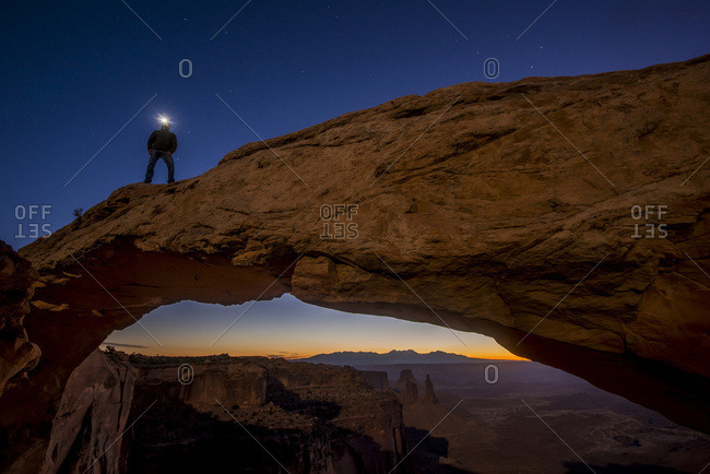 Man with a headlamp standing on top of Mesa Arch at Canyonlands National Park, Utah, USA
