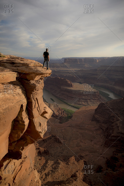A man looking out over a canyon and river in Dead Horse Point State Park, Utah