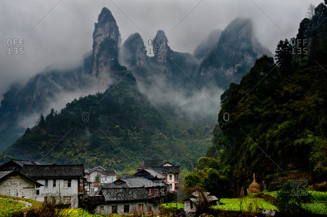 Rock karsts in fog behind a small Chinese village