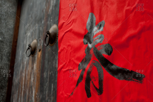 Chinese symbol on red, beside an old door