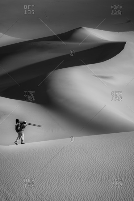 A man hiking with camera in Great Sand Dunes National Park in Colorado, USA