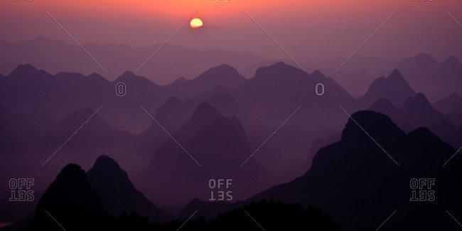Mountains in early morning fog with the sun rising in  Gulilin, Guangxi, China