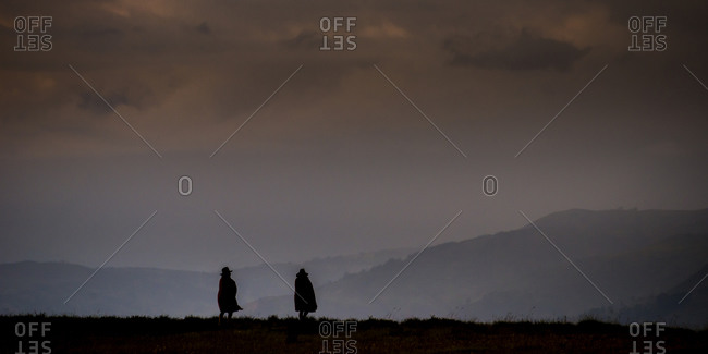 Silhouettes of two men at the Cordillera Blanca Mountains under a stormy sky in Huraz, Ancash, Peru