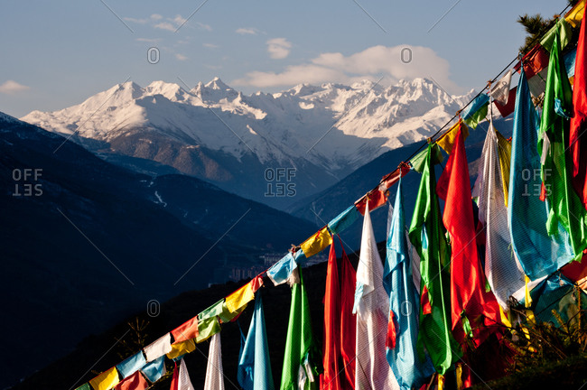 Prayer flags in front of snow covered mountains, Kangding, Sichuan, China