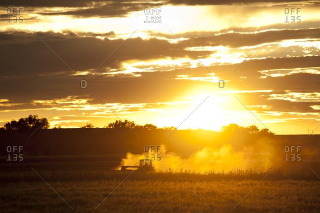 Tractor farming at sunset in La Junta, Colorado, USA