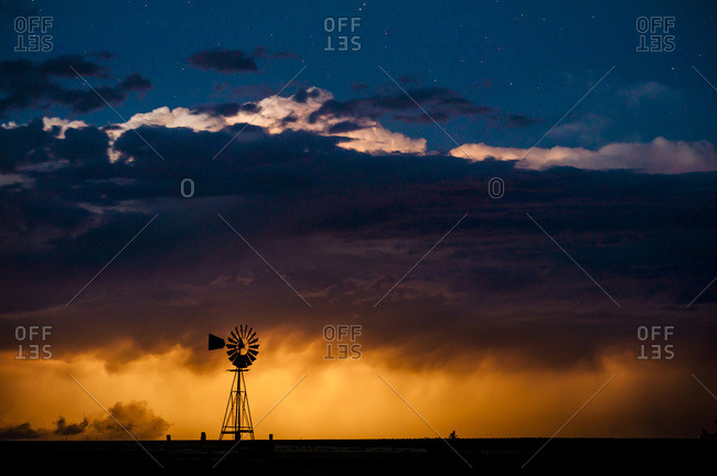 A windmill in a thunderstorm in the distance in  La Junat, Colorado, USA