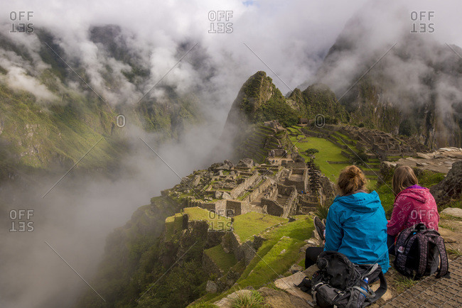 Two young women looking over the ruins of Machu Picchu in  Peru