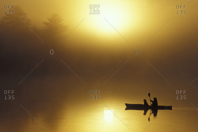 Silhouette of a woman sea kayaking with a dog at sunrise on Oxtongue Lake, Muskoka, Ontario, Canada