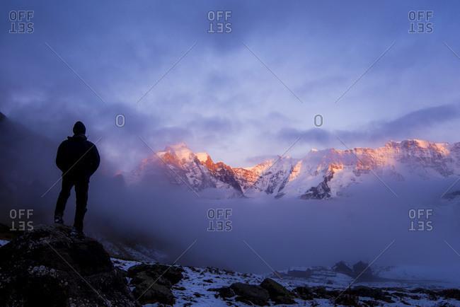 Hiker observing the mountains at sunset near Murren, Switzerland