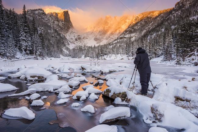 Man taking photos of the frozen  Dream Lake in Rocky Mountain National Park, Estes Park, Colorado, USA