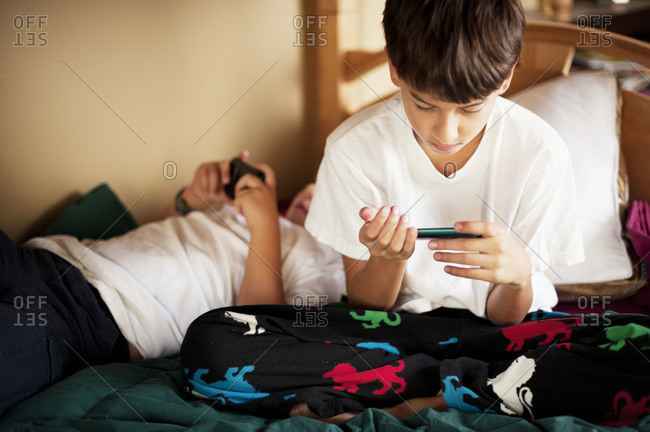 Two brothers playing videogames in bed