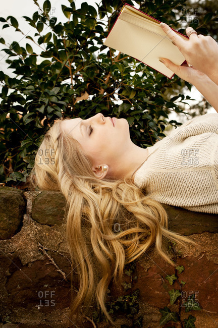A woman lays on a stone wall and reads