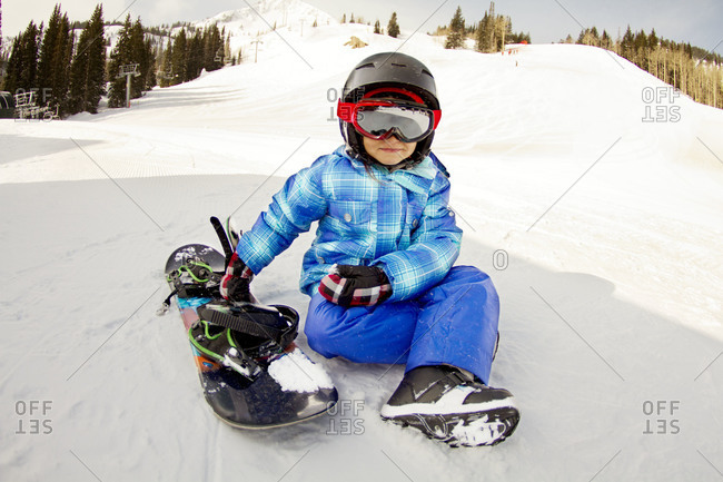 A young girl sits beside her snowboard