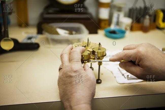 The hands of a clockmaker repairing a clock