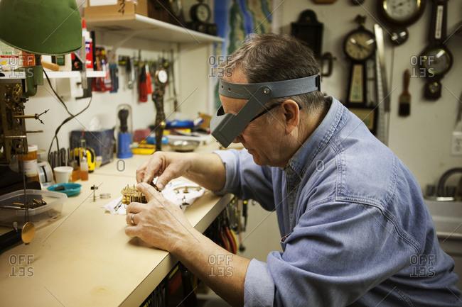 A clock maker repairing a clock motor