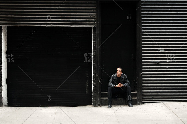 A man sits in a stairway on the street