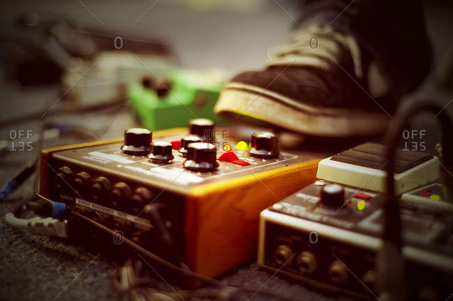 A musician steps on a guitar pedal