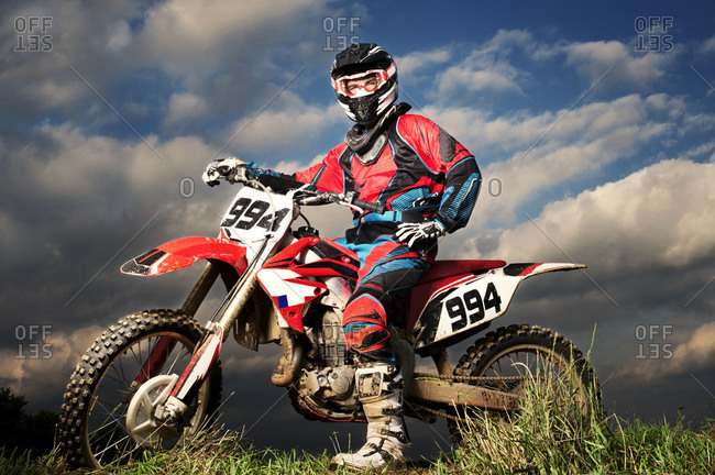 Motocross rider posing on his bike