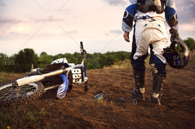 Motocross rider walking away after a crash