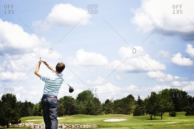 Back view of golfer teeing off