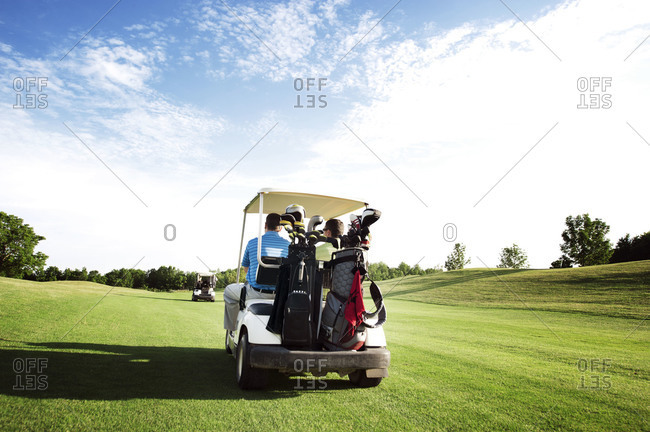 Men riding in a golf cart in a golf course