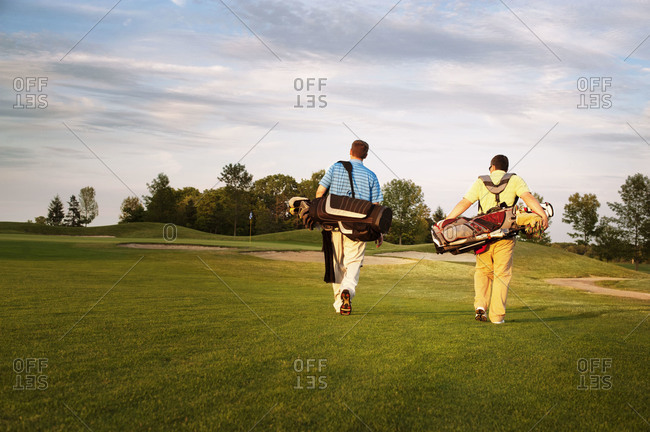 Back view of men walking in a golf course at sunset