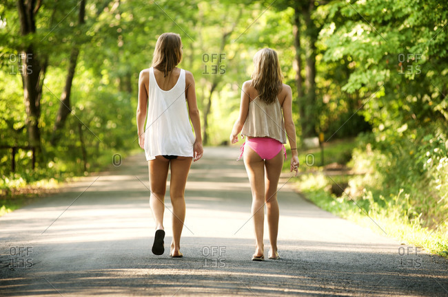 Back view of young women walking down the road