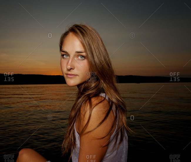 Portrait of young woman by a lake at sunset