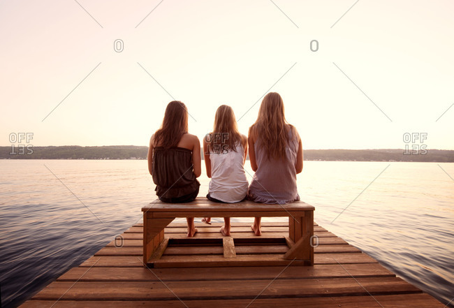 Back view of friends sitting on a jetty