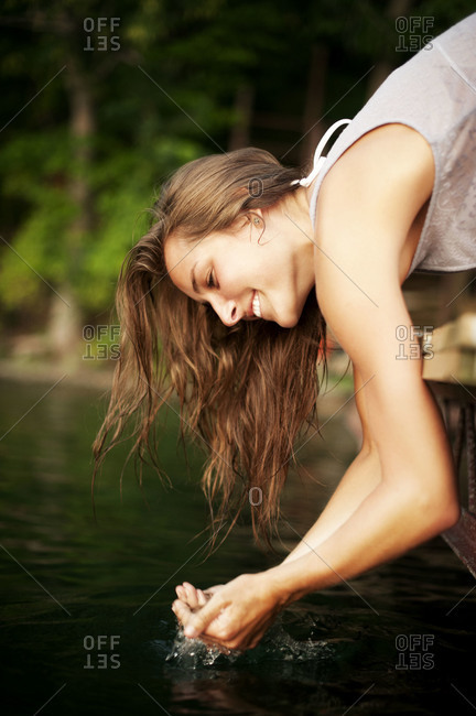Young woman dipping her hands in a lake