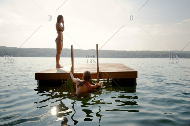 Woman climbing on a floating dock in a lake