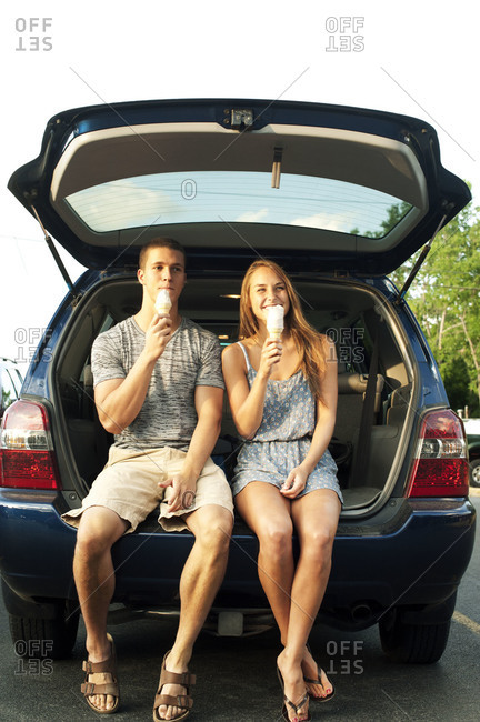 Couple eating ice cream at the trunk of a car