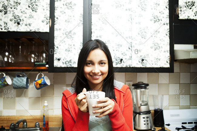 Young woman holding a mug in a kitchen