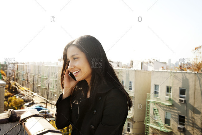 Young woman using mobile phone on urban rooftop