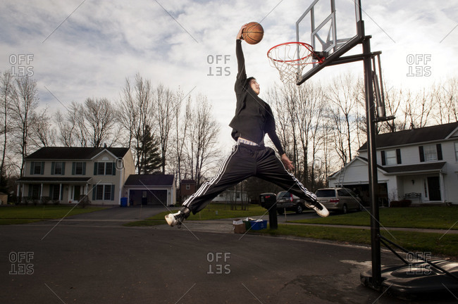Teenager dunking a basketball into the hoop