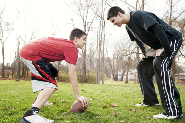 Two boys playing football in the backyard