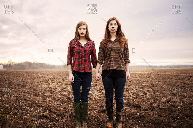 Young women holding hands in a field