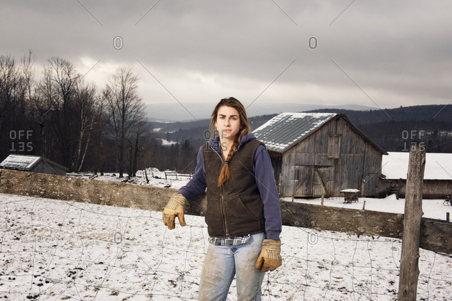 Portrait of woman leaning against a fence at a farm