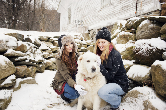 Young women petting a dog in the snow