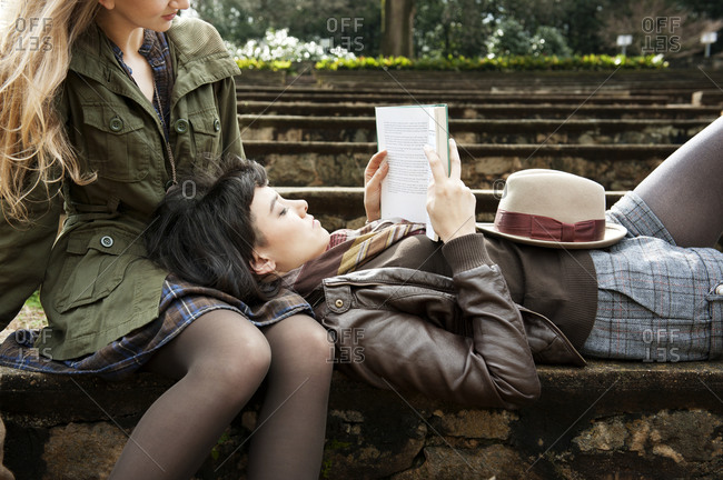 Friends reading a book together in a park