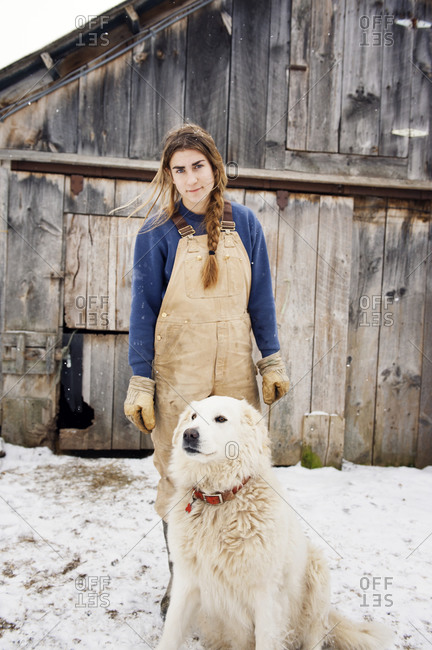 Portrait of woman with a dog at a farm