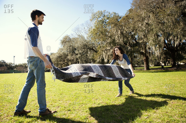 Couple laying down a blanket in a park