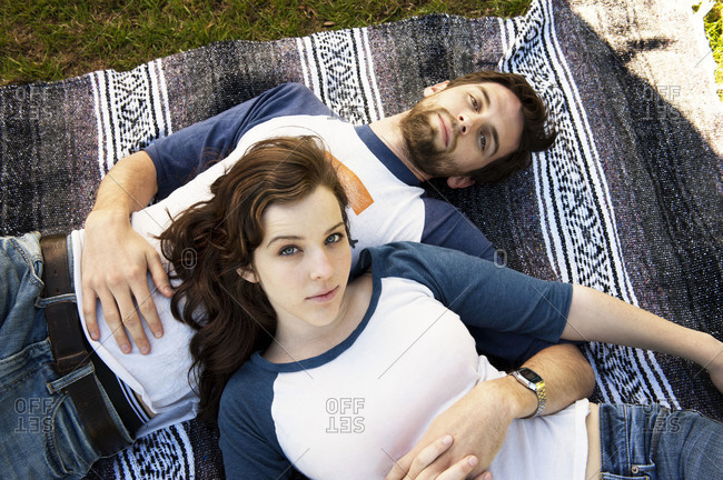 Top view of couple lying on blanket in a park