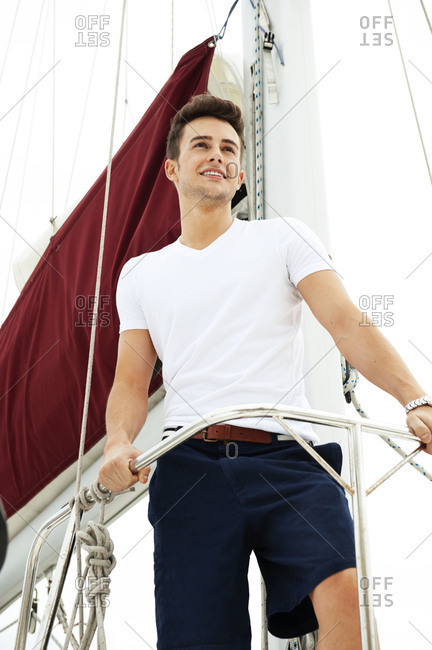 Portrait of young man standing at the prow of a sailboat