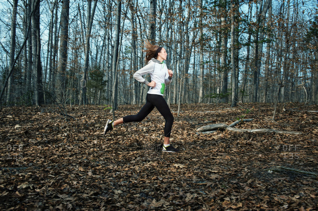 Young woman running in a forest