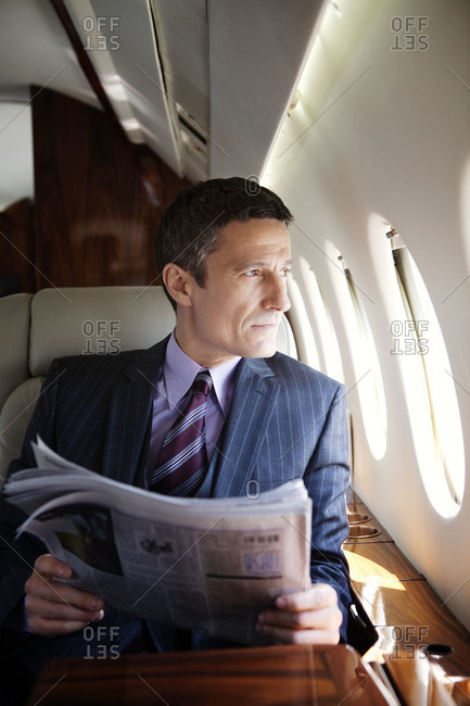 Businessman looking out the window of an airplane