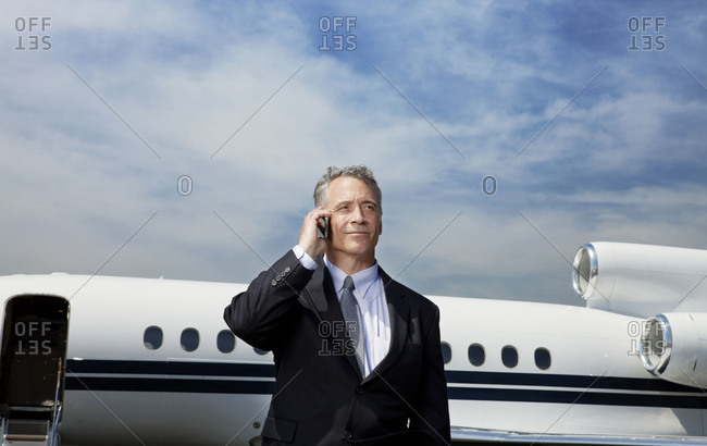 Businessman talking on the phone at a private jet