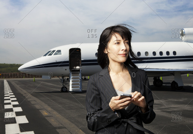 Businesswoman holding a smartphone at the airport