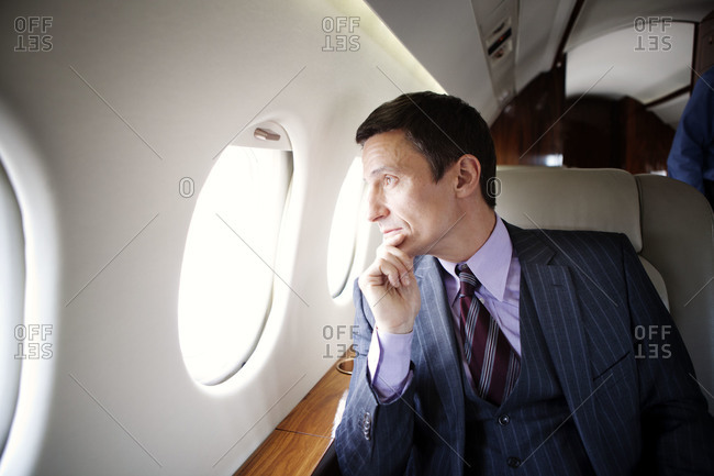 Businessman staring out of window of a private jet