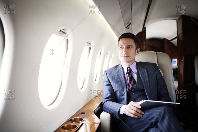 Businessman holding a tablet on a private jet